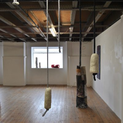 Installation view - (windowsill) Soap Tubes I - III (LB); (corner) Soft Rocks (LB); (left hand wall) Boiler Suit Relief No.4 (SG); (floor) Rag Plinth (Circular) (SG); (foreground) Soap On A Rope (LB)